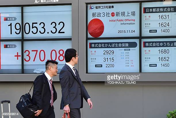 Pedestrians walk past a share prices board displaying prices of Japan Post Holdings Japan Post Bank and Japan Post Insurance in Tokyo on November 4...