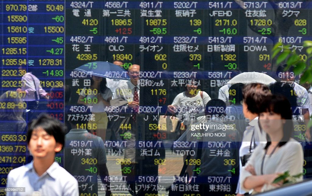 Pedestrians walk past a share prices board of the Tokyo Stock Exchange in Tokyo on August 1 2014 Tokyo stocks opened 070 percent lower on August 1...