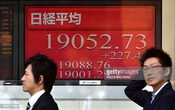 Pedestrians walk past a share prices board showing the numbers on the Nikkei 225 at the Tokyo Stock Exchange in Tokyo on October 26 2015 Tokyo shares...