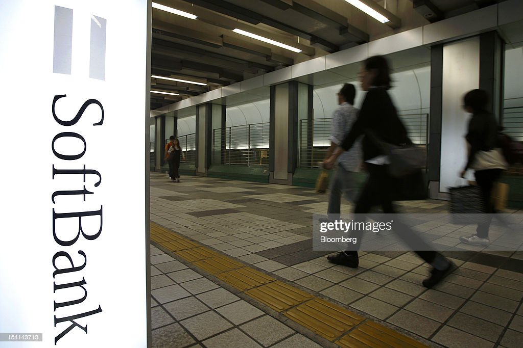 Pedestrians walk past a sign bearing the Softbank Corp. logo outside the company's store in Tokyo, Japan, on Monday, Oct. 15, 2012. Softbank agreed to pay $20.1 billion to acquire about a 70 percent stake in Sprint Nextel Corp. as Japan's third-biggest mobile-phone operator seeks growth overseas amid a declining local market. Photographer: Kiyoshi Ota/Bloomberg via Getty Images