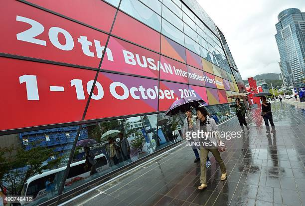 Pedestrians walk past a sign for the Busan International Film Festival at the Busan Cinema Center in Busan on October 1 2015 Stars from Asia and...