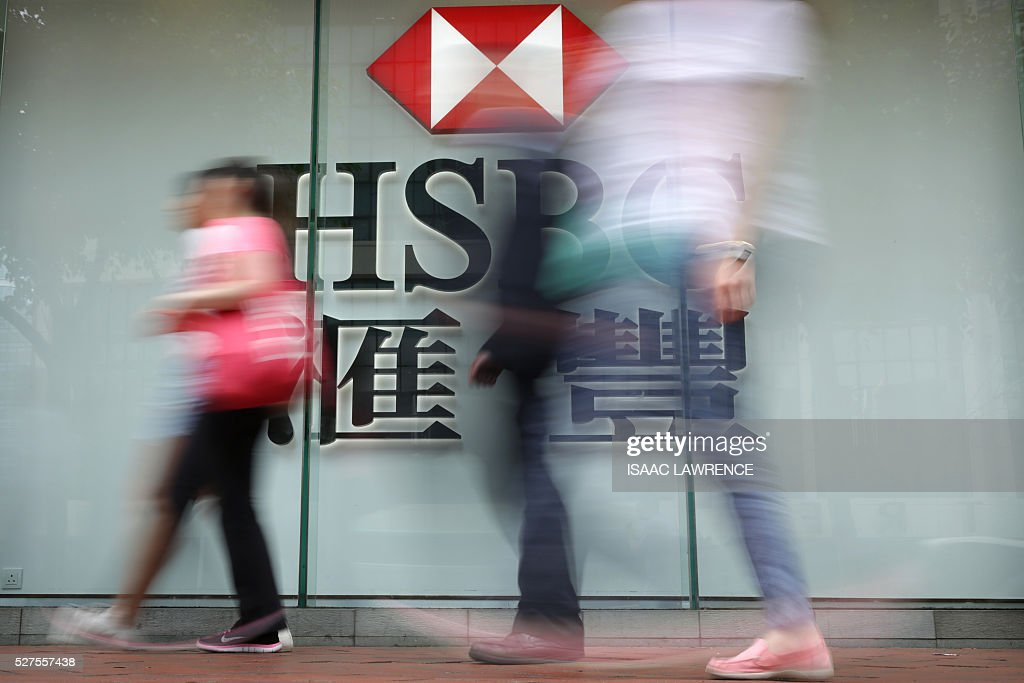 Pedestrians walk past a sign for the Hong Kong and Shanghai Banking Corporation (HSBC) bank in Hong Kong on May 3, 2016. HSBC's net profit was down 18 percent at 4.3 billion USD in the first quarter, the bank said on May 3, affected by 'extreme levels' of market volatility early in the year. LAWRENCE