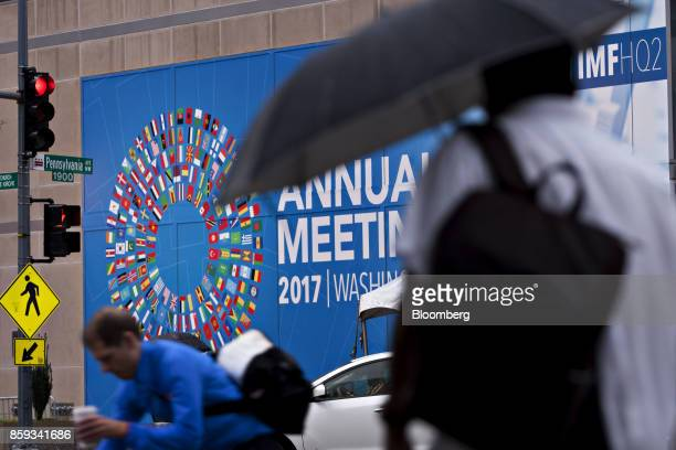 Pedestrians walk past a sign for the International Monetary Fund and World Bank Group Annual Meetings in Washington DC US on Monday Oct 9 2017 The...