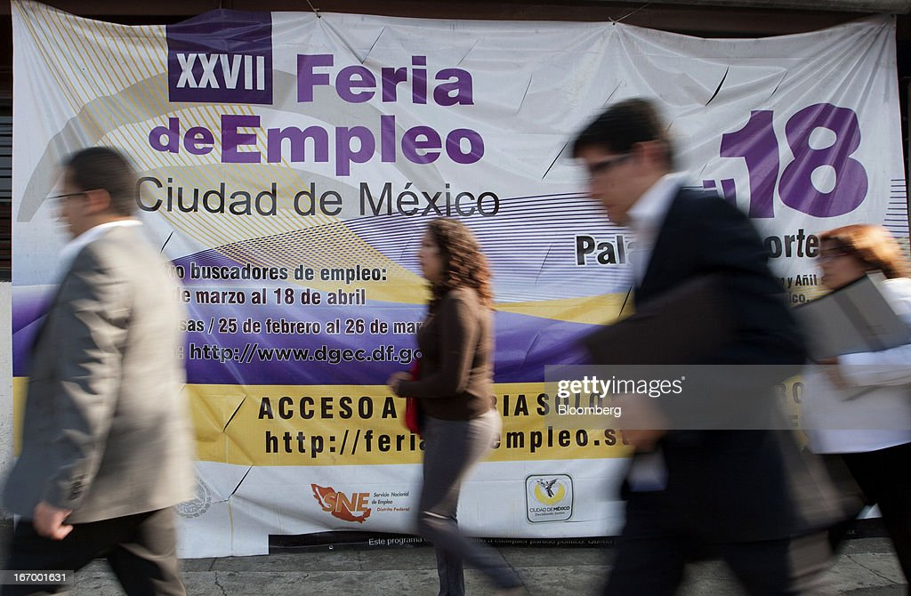 Pedestrians walk past a sign for the XXVII job fair at the Palacio de los Deportes in Mexico City, Mexico, on Thursday, April 18, 2013. Mexico created 53,994 permanent and temporary urban jobs in March, according to reports from the Mexican Social Security Institute (IMSS). Photographer: Susana Gonzalez/Bloomberg via Getty Images