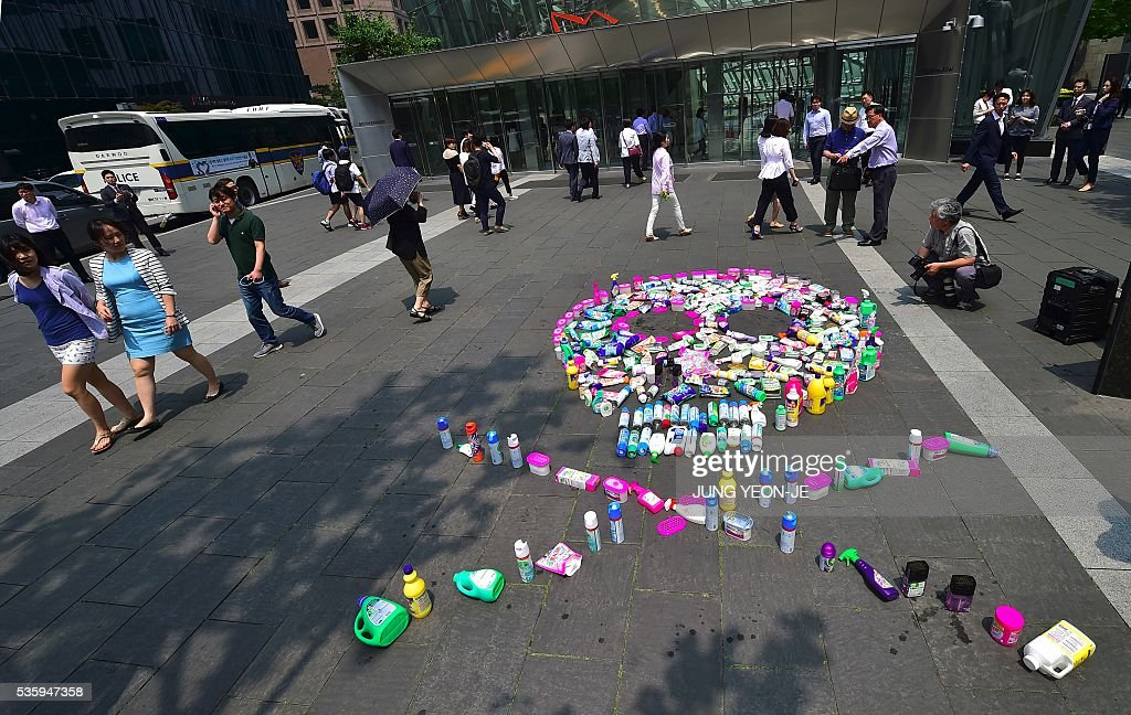 Pedestrians walk past a skull made of Oxy products during a campaign to boycott Reckitt Benckiser, whose Korean unit -- Oxy Reckitt Benckiser -- made humidifier disinfectants and sterilizers blamed for the deaths of more than 100 people in South Korea, outside the company's Seoul office in Seoul on May 31, 2016. Most of the victims were found to have used Oxy Ssak Ssak, a liquid humidifier disinfectant sold by Reckitt Benckiser in South Korea from 2001, that has been blamed for around 103 deaths -- mostly women and children. / AFP / JUNG