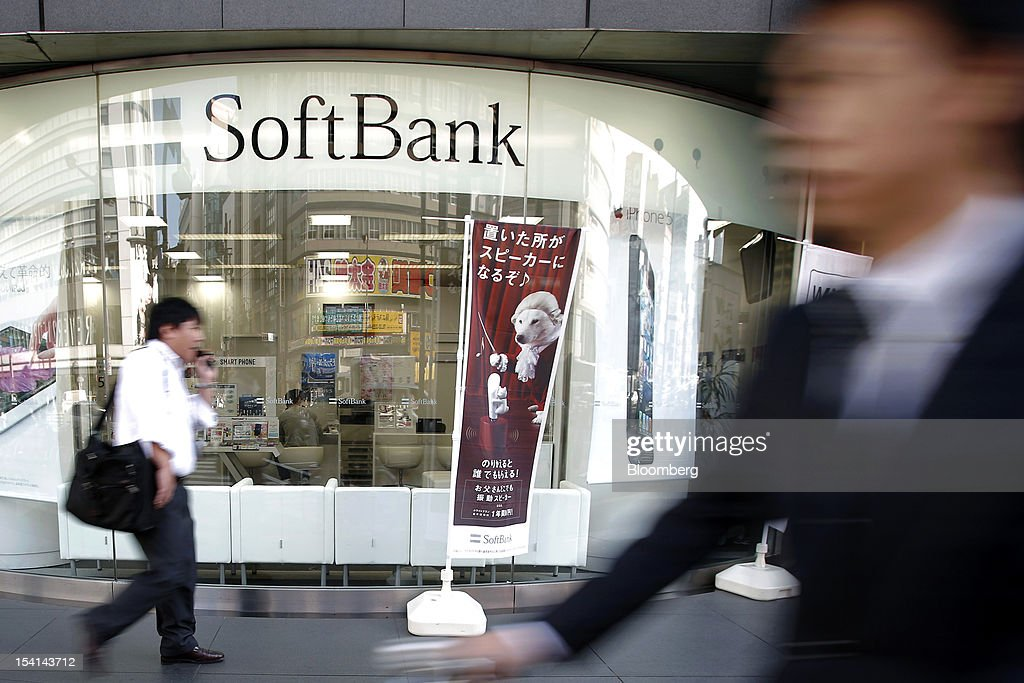 Pedestrians walk past a Softbank Corp. store in Tokyo, Japan, on Monday, Oct. 15, 2012. Softbank agreed to pay $20.1 billion to acquire about a 70 percent stake in Sprint Nextel Corp. as Japan's third-biggest mobile-phone operator seeks growth overseas amid a declining local market. Photographer: Kiyoshi Ota/Bloomberg via Getty Images