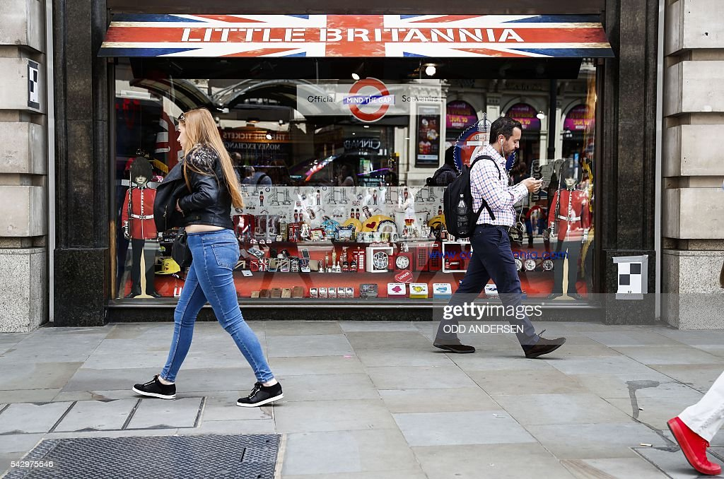 Pedestrians walk past a souvenir shop displaying United Kingdom themed merchandise in central London on June 25, 2016, after the announcement that the UK had voted on June 23 to leave the European Union in a national referendum. The result of Britain's June 23 referendum vote to leave the European Union (EU) has pitted parents against children, cities against rural areas, north against south and university graduates against those with fewer qualifications. London, Scotland and Northern Ireland voted to remain in the EU but Wales and large swathes of England, particularly former industrial hubs in the north with many disaffected workers, backed a Brexit. / AFP / Odd ANDERSEN