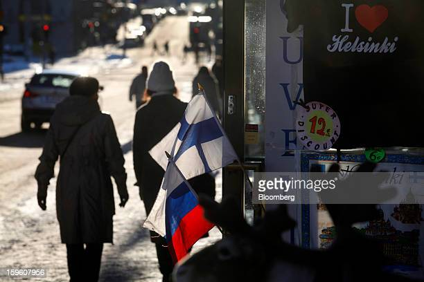 Pedestrians walk past a souvenir store selling Finnish right and Russian national flags in Helsinki Finland on Thursday Jan 17 2013 The pace of...