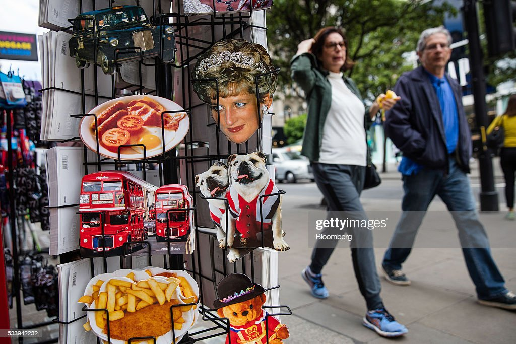 Pedestrians walk past a souvenir store selling postcards of London buses, fish and chips, British bulldogs and a fried bacon and egg breakfast on Oxford Street in London, U.K., on Tuesday, May 24, 2016. U.K. retail sales began the second quarter with more momentum than economists forecast. Photographer: Simon Dawson/Bloomberg via Getty Images