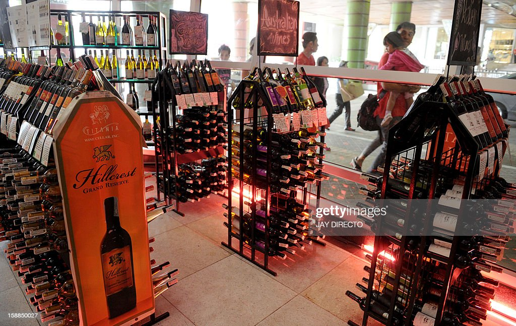 Pedestrians walk past a stall selling alcoholic beverages at a mall in Manila on January 1, 2013. A 'sin tax' on cigarettes and alcohol dampened the New Year party spirit when it was introduced in the Philippines on January 1, as part of a government bid to boost finances.
