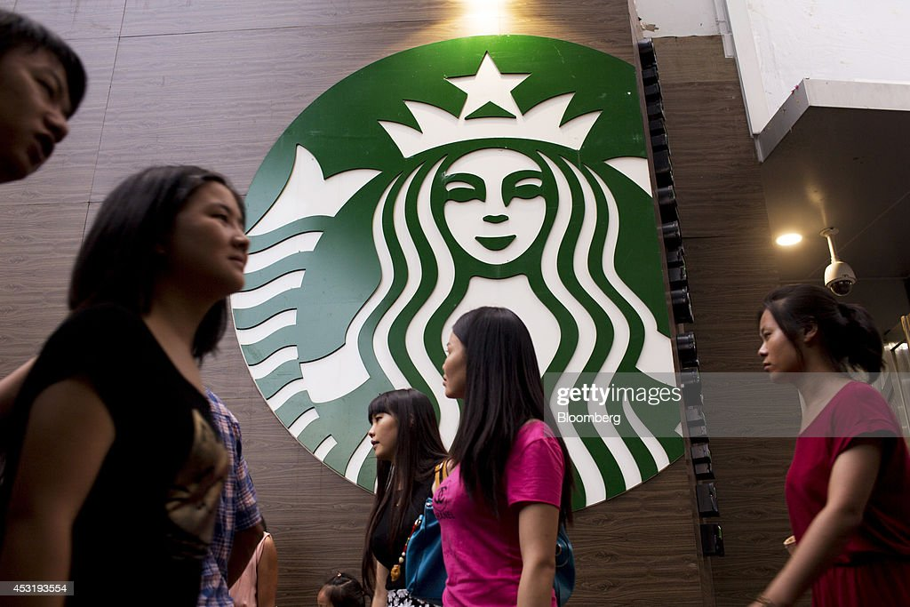 Pedestrians walk past a Starbucks Corp. store in the Luohu district of Shenzhen, China, on Monday, Aug. 4, 2014. Starbucks says it's taking measures to ensure food quality meets China and international standards in statement on an official microblog. Photographer: Brent Lewin/Bloomberg via Getty Images