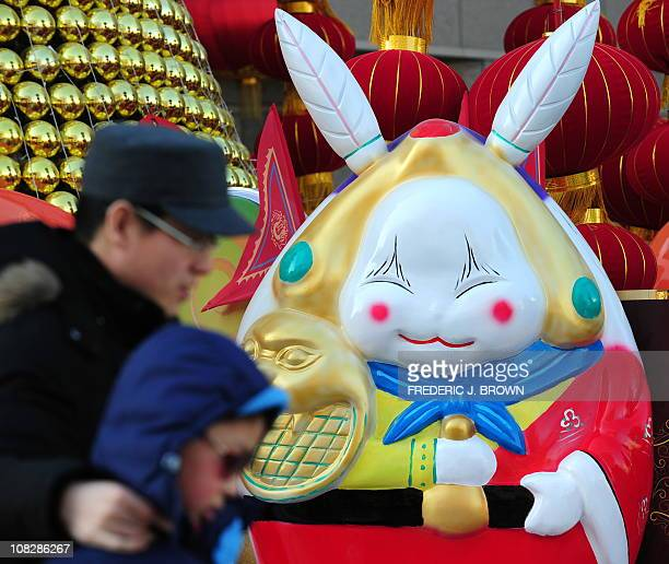 Pedestrians walk past a statue on January 18 2011 of Lord Rabbit known as Tuer Ye a traditional icon of the MidAutum Festival but becoming ever...