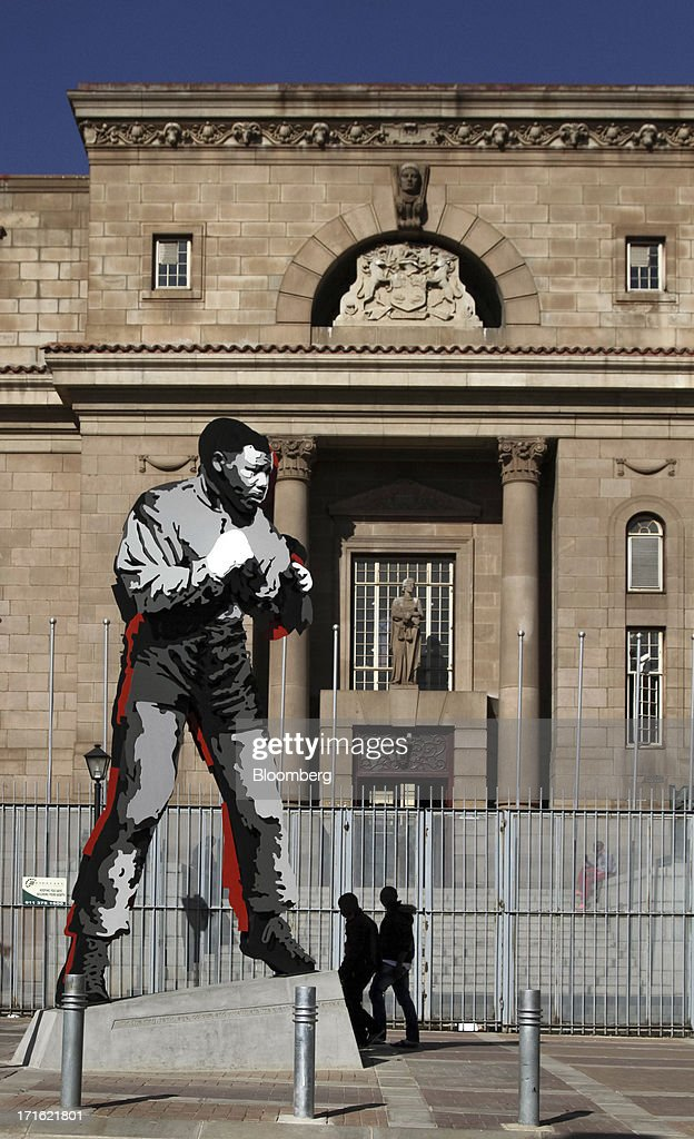 Pedestrians walk past a steel statue to former South African president Nelson Mandela positioned outside the magistrates law courts in Johannesburg, South Africa, on Thursday, June 27, 2013. South African President Jacob Zuma cancelled a trip to neighbouring Mozambique today after visiting Nelson Mandela, who remains critically ill in the hospital. Photographer: Nadine Hutton/Bloomberg via Getty Images