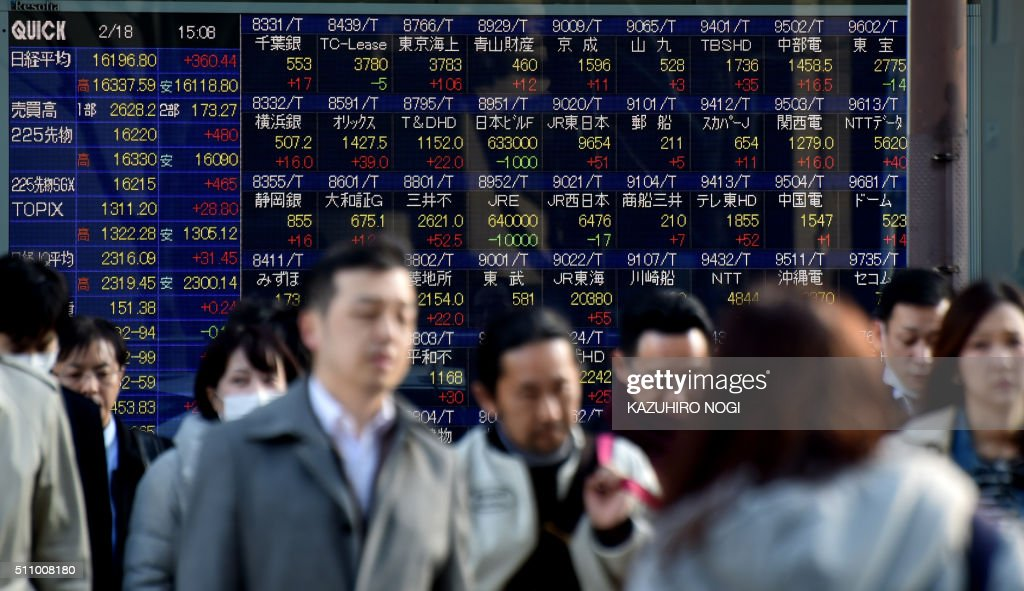 Pedestrians walk past a stock prices board showing numbers of the Tokyo Stock Exchange in Tokyo on February 18 2016 Tokyo shares closed more than two...