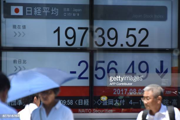 Pedestrians walk past a stock quotation board flashing the Nikkei 225 key index of the Tokyo Stock Exchange in front of a securities company in Tokyo...
