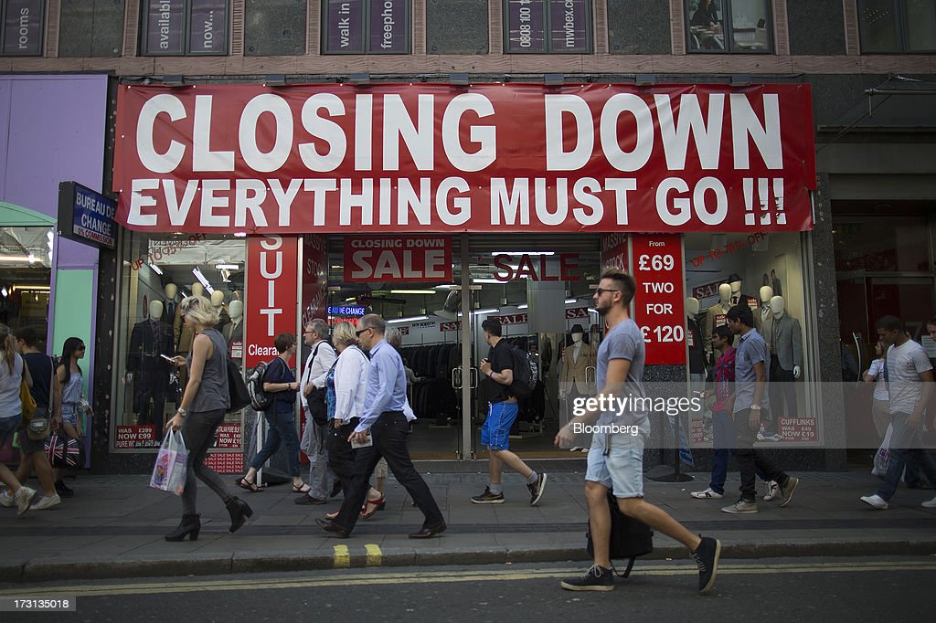 Pedestrians walk past a store advertising a 'Closing Down' sale in London, U.K., on Monday, July 8, 2013. Britain's economy could be in line for a period of 'strong catch-up growth' once it gets through the current weakness, according to Capital Economics Ltd. Photographer: Simon Dawson/Bloomberg via Getty Images