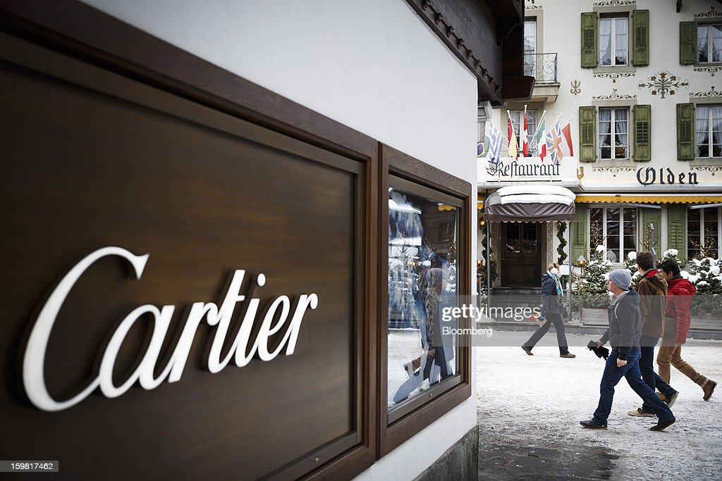 Pedestrians walk past a store advertising the Cartier jewelry brand in Gstaad, Switzerland, on Saturday, Jan. 19, 2013. Options traders are pushing the cost of bearish wagers on Swiss shares to the lowest level in almost seven years amid optimism a decline in the franc versus the euro will benefit the nation's exporters. Photographer: Valentin Flauraud/Bloomberg via Getty Images