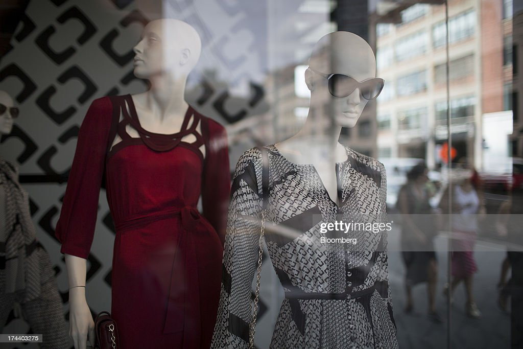 Pedestrians walk past a store window display in New York, U.S., on Wednesday, July 24, 2013. The U.S. Conference Board is scheduled to release consumer confidence figures on July 30. Photographer: Scott Eells/Bloomberg via Getty Images