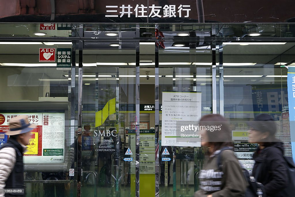 Pedestrians walk past a Sumitomo Mitsui Banking Corp. branch in Tokyo, Japan, on Tuesday, Nov. 13, 2012. Sumitomo Mitsui Financial Group Inc. is scheduled to announce first-half earnings results on Nov. 14. Photographer: Kiyoshi Ota/Bloomberg via Getty Images