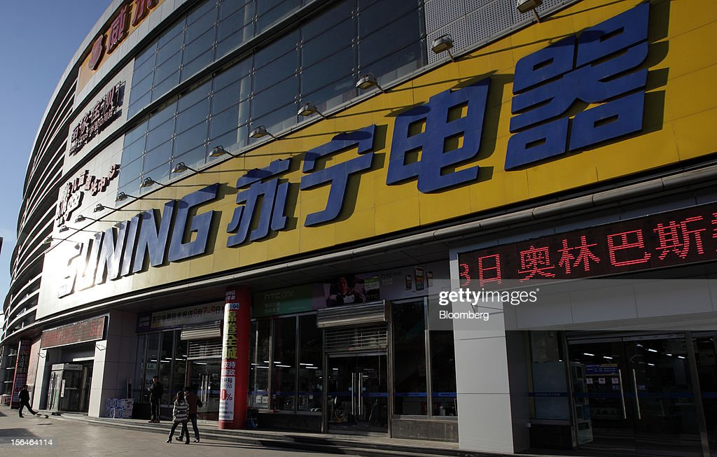 Pedestrians walk past a Suning Appliance Co. store in Beijing, China, on Tuesday, Nov. 13, 2012. Suning is China's biggest electronics retailer by market value. Photographer: Tomohiro Ohsumi/Bloomberg via Getty Images