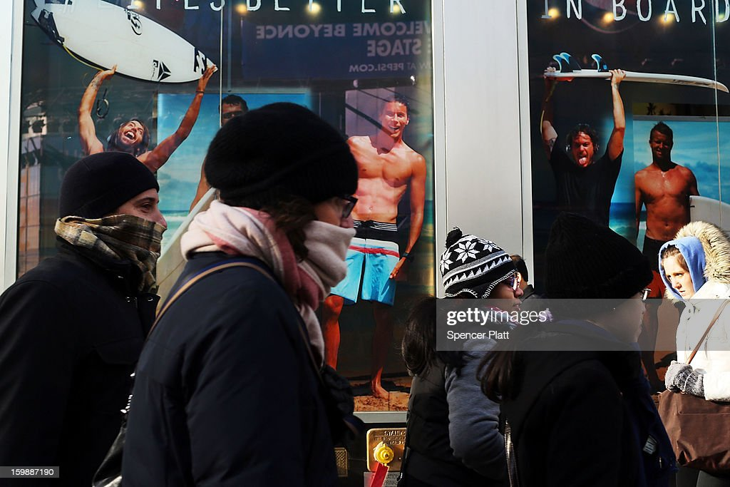 Pedestrians walk past a surfing store on one of the coldest days of the year on January 22, 2013 in New York City. New York, and much of the Northeast, will be experiencing colder-than-usual temperatures for the remainder of the week with temperatures in the 20's and a wind chill feeling in the single digits.