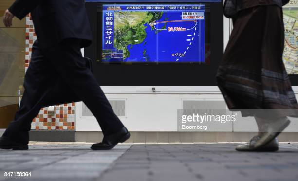 Pedestrians walk past a television screen displaying a map of Japan and the Korean Peninsula in a news program reporting on North Korea's missile...