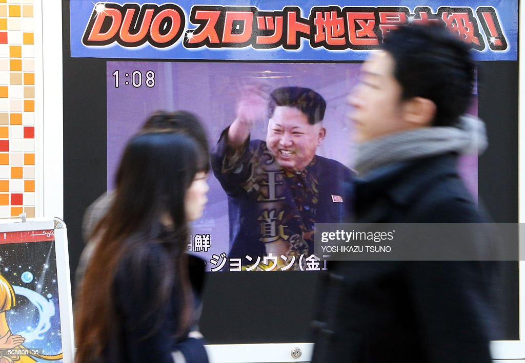 Pedestrians walk past a TV along a street in Tokyo showing North Korea's leader Kim Jong-Un (C) and a report on North Korea's rocket launch on February 7, 2016. North Korea launched a long-range rocket on February 7, violating UN resolutions and doubling down against an international community already determined to punish Pyongyang for a nuclear test last month. AFP PHOTO / Yoshikazu TSUNO / AFP / YOSHIKAZU TSUNO