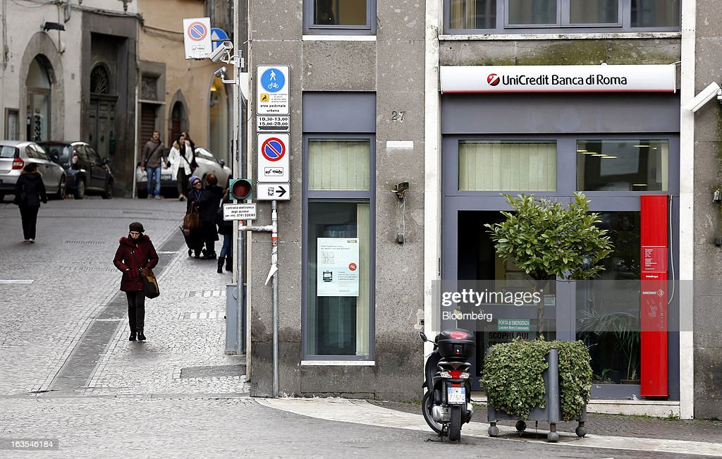 Pedestrians walk past a UniCredit SpA bank branch in Viterbo, Italy, on Monday, March 11, 2013. Intesa Sanpaolo SpA and UniCredit SpA are among Italian banks due to report losses for the fourth quarter this week, as the economic contraction meant more clients failed to repay their debts. Photographer: Alessia Pierdomenico/Bloomberg via Getty Images