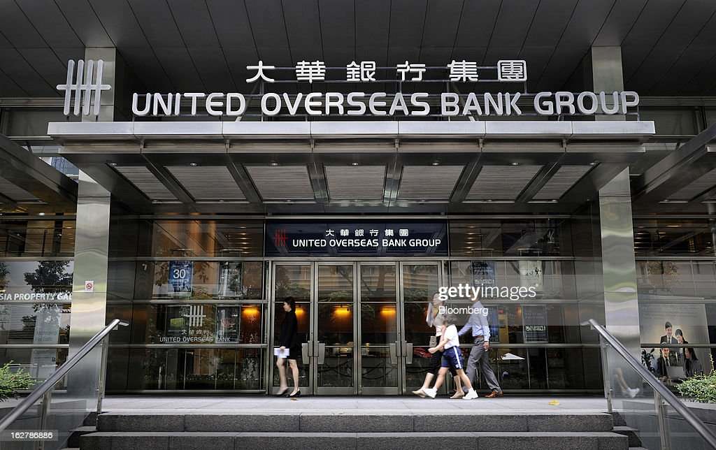 Pedestrians walk past a United Overseas Bank Ltd. (UOB) branch in Singapore, on Wednesday, Feb. 27, 2013. UOB is scheduled to announce full year results today. Photographer: Munshi Ahmed/Bloomberg via Getty Images