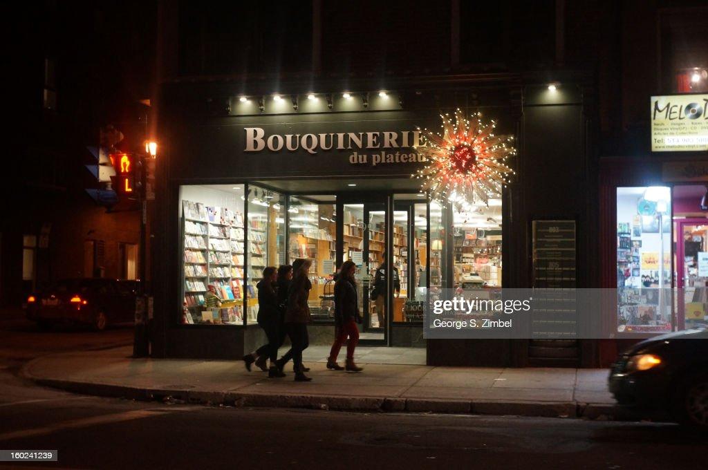 Pedestrians walk past a used bookstore, Bouquinerie du Plateau, on the corner of Rue Saint-Hubert and Avenue du Mont-Royal E, Montreal, Quebec, Canada, 2013.