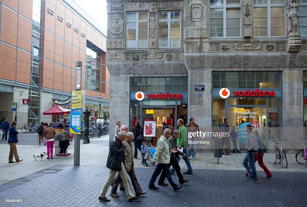 Pedestrians walk past a Vodafone store operated by Vodafone Group Plc in Leipzig, Germany, on Thursday, Sept. 12, 2013. Vodafone Group Plc's 7.7 billion-euro ($10.2 billion) bid for Kabel Deutschland Holding AG cleared a major hurdle by winning the backing of at least 75 percent of the German company's shareholders. Photographer: Krisztian Bocsi/Bloomberg via Getty Images