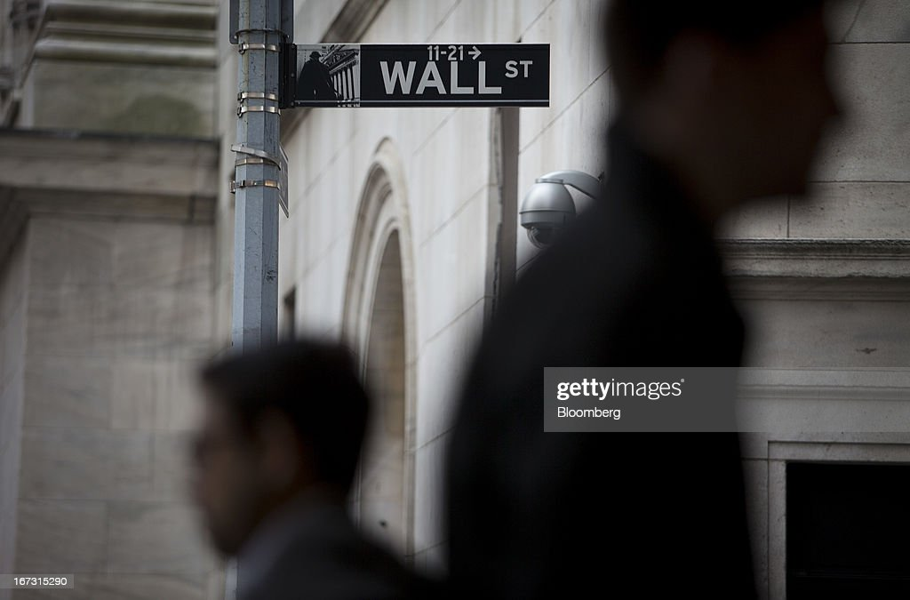 Pedestrians walk past a Wall Street sign and security camera in front of the New York Stock Exchange (NYSE) in New York, U.S., on Wednesday, April 24, 2013. U.S. stocks were little changed, after the Standard & Poor's 500 Index gained for a third day, as investors watched earnings at companies from Boeing Co. to Apple Inc. Photographer: Scott Eells/Bloomberg via Getty Images