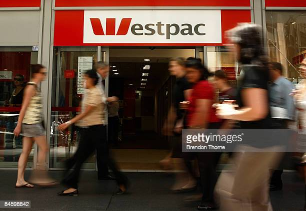 Pedestrians walk past a Westpac branch in Sydney as economists wait to see if The Reserve Bank of Australia cut official interest rates today at the...