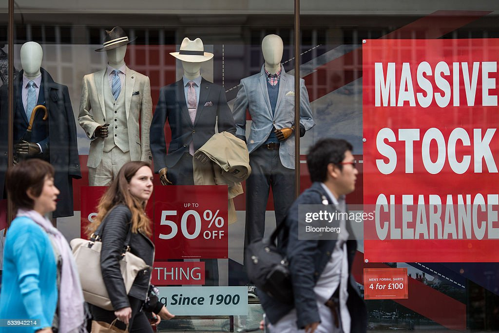 Pedestrians walk past a window display advertising a 50 percent discounts and stock clearance offers at an Austin Reed menswear store on Regent Street in London, U.K., on Tuesday, May 24, 2016. U.K. retail sales began the second quarter with more momentum than economists forecast. Photographer: Simon Dawson/Bloomberg via Getty Images