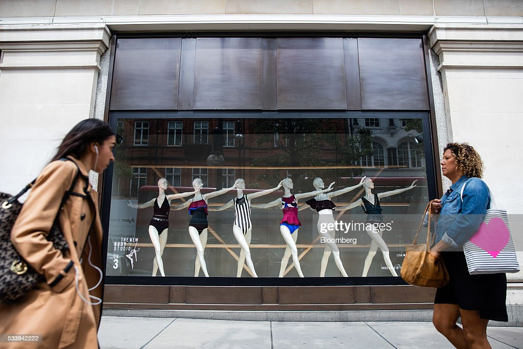 Pedestrians walk past a window display of women's bathing suits at the Selfridges Plc department store on Oxford Street in London, U.K., on Tuesday, May 24, 2016. U.K. retail sales began the second quarter with more momentum than economists forecast. Photographer: Simon Dawson/Bloomberg via Getty Images