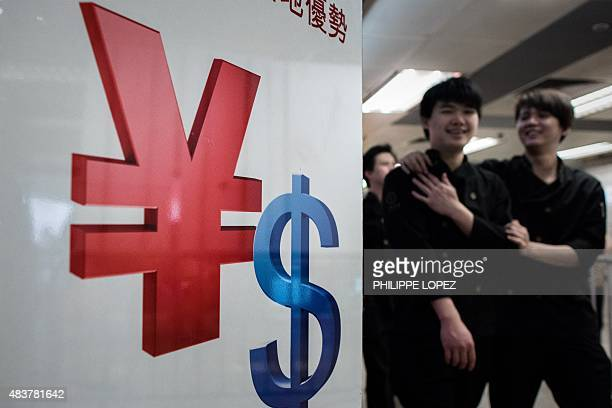 Pedestrians walk past a yuan and a US dollar currency sign in Hong Kong on August 13 2015 China cut the reference rate for its currency for the third...