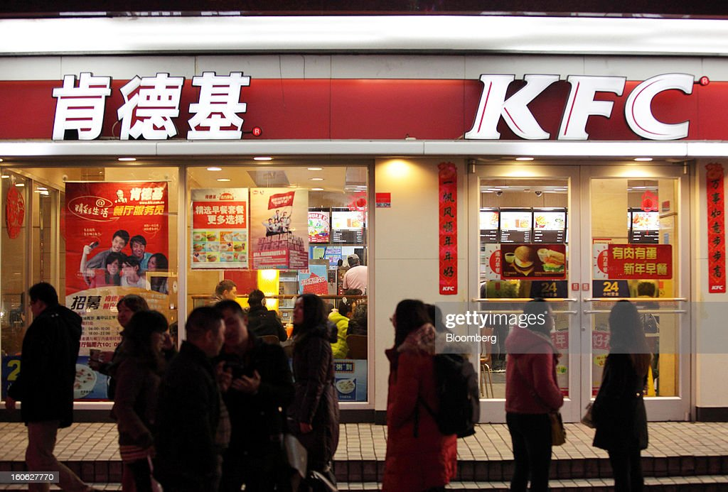 Pedestrians walk past a Yum! Brands Inc. KFC restaurant at night in the East Nanjing Road shopping area of Shanghai, China, on Friday, Feb. 1, 2013. China's services industries grew at the fastest pace since August as gains in retailing and construction aid government efforts to drive a recovery in the world's second-biggest economy. Photographer: Tomohiro Ohsumi/Bloomberg via Getty Images