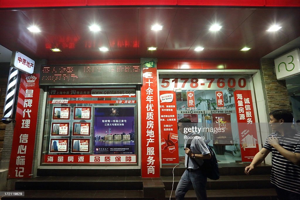 Pedestrians walk past advertisements for residential properties for sale displayed in the window of a real estate agent's office in Shanghai, China, on Monday, July 1, 2013. China's President Xi Jinping said officials shouldn't be judged solely on their record in boosting gross domestic product, the latest signal that policy makers are prepared to tolerate slower economic expansion. Photographer: Tomohiro Ohsumi/Bloomberg via Getty Images