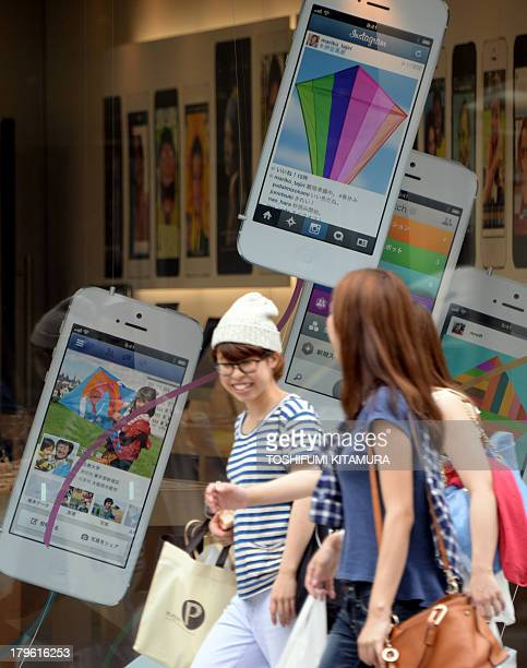 Pedestrians walk past advertisements for the iPhone 5 at the Apple store in central Tokyo on September 6 2013 Japan's top mobile carrier NTT DoCoMo...