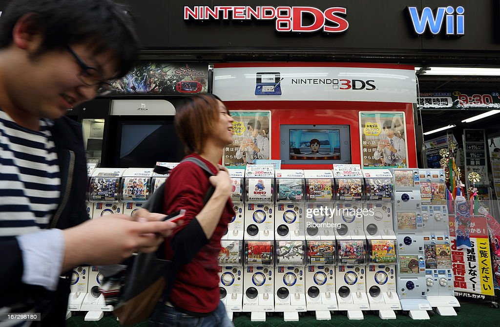 Pedestrians walk past an advertisement for Nintendo Co.'s 3DS handheld game console outside an electronics store in Tokyo, Japan, on Tuesday, April 23, 2013. Nintendo, the world's largest maker of video-game machines, will announce earnings on April 24. Photographer: Tomohiro Ohsumi/Bloomberg via Getty Images
