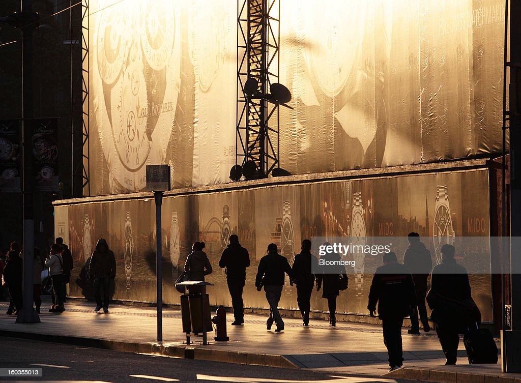 Pedestrians walk past an advertisement reflecting the setting sun in the East Nanjing Road shopping area of Shanghai, China, on Monday, Jan. 28, 2013. China's economic growth accelerated for the first time in two years as government efforts to revive demand drove a rebound in industrial output, retail sales and the housing market. Photographer: Tomohiro Ohsumi/Bloomberg via Getty Images