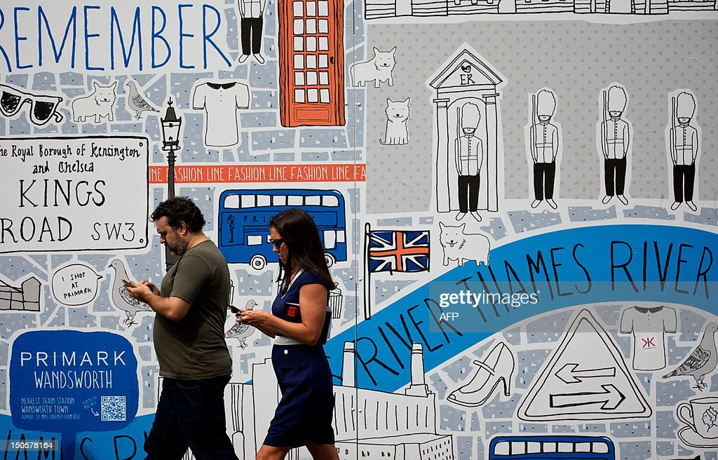 Pedestrians walk past an advertising board using mobile phones in central London on August 22, 2012. Britain will have access to superfast 4G mobile Internet services by the end of the year, communications watchdog Ofcom said on Tuesday after approving its launch by telecoms providers Orange and T-Mobile. AFP PHOTO / ANDREW COWIE