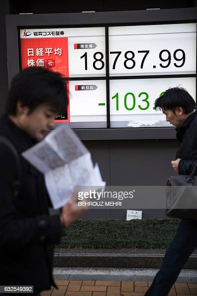 Pedestrians walk past an electric quotation board flashing numbers of the Nikkei key index of the Tokyo Stock Exchange in Tokyo on January 24 2017...