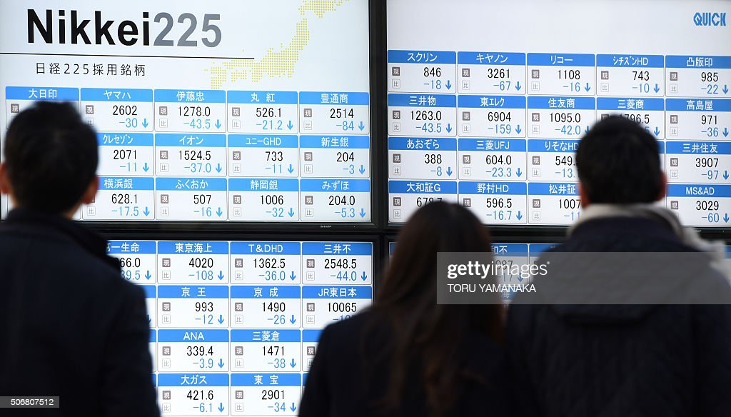 Pedestrians walk past an electric quotation board flashing share prices of the Tokyo Stock Exchange in front of a securities company in Tokyo on...