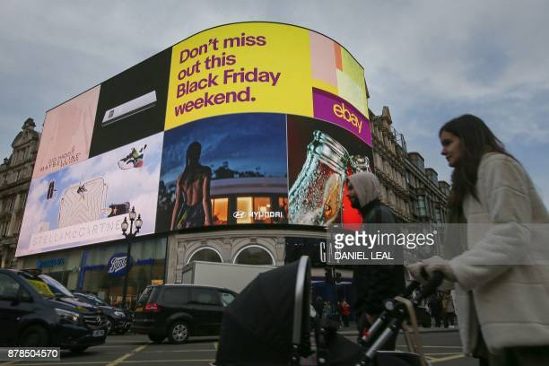 Pedestrians walk past an electronic advert for 'Black Friday' sales discounts on Ebay at Piccadilly Circus in London on November 24 2017 Black Friday...