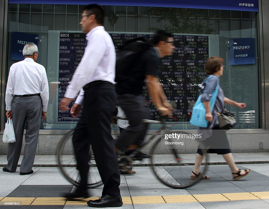 Pedestrians walk past an electronic board outside a securities firm in Tokyo Japan on Friday Aug 21 2015Japanese stocks plunged with the Topix index...