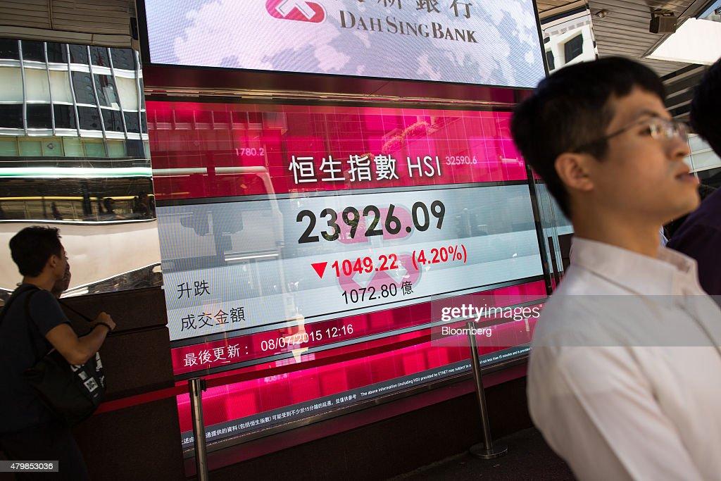 Pedestrians walk past an electronic display showing the Hang Seng Index figure in Hong Kong China on Wednesday July 8 2015 Hong Kong's benchmark...