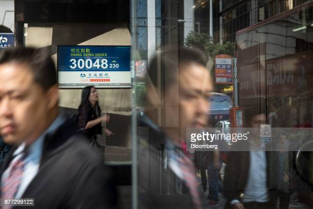 Pedestrians walk past an electronic screen displaying the Hang Seng Index in Hong Kong China on Wednesday Nov 22 2017 Hong Kong's benchmark equity...
