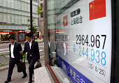 Pedestrians walk past an electronic stock board displaying the Shanghai Composite Index outside a securities firm in Tokyo Japan on Tuesday Aug 25...