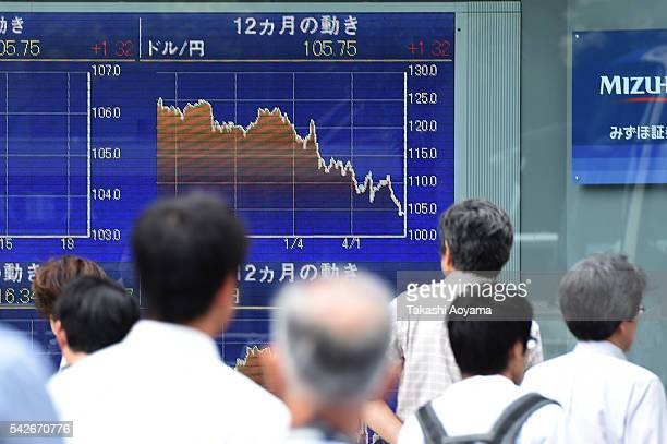 Pedestrians walk past an electronic stock board displaying the exchange rate of the yen against the US dollar outside a securities firm on June 24...